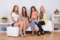 Young ladies sitting on a couch at home Royalty Free Stock Image