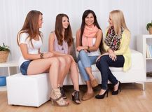 Young ladies sitting on a couch at home Stock Photography