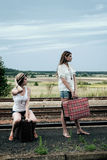 Young ladies with suitcases. Young ladies with old suitcases on a platform Stock Image