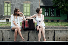 Young ladies with suitcases. Young ladies with old suitcases on a platform Stock Photos