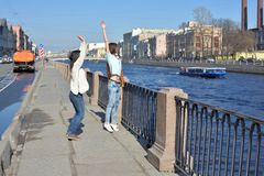 Young ladies tourists in Saint Peteresburg Russia enjoy summer on a sunny day and greet sightseeing boats on Fontanka river, stock photo