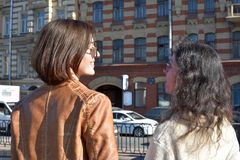 Young ladies tourists in Saint Petersburg Russia stand on a bridge at a yellow buildings square and watch architectural details of. A building, sunny day, blue stock photography
