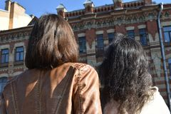 Young ladies tourists in Saint Petersburg Russia stand on a bridge at a yellow buildings square and watch architectural details of. A building, sunny day, blue royalty free stock photography