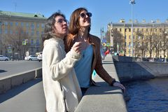 Young ladies tourists in Saint Petersburg Russia stand on a bridge at a yellow buildings square and watch architectural details of stock image