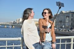 Young ladies tourists in Saint Petersburg Russia take selfies on a wooden bridge in the historical city center stock photos
