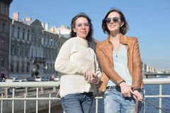Young ladies tourists in Saint Petersburg Russia take selfies on a wooden bridge in the historical city center royalty free stock image