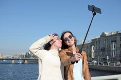 Young ladies tourists in Saint Petersburg Russia take selfies on a wooden bridge in the historical city center. Have fun and smile on a sunny day, blue sky royalty free stock photo
