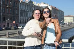 Young ladies tourists in Saint Petersburg Russia take selfies on a wooden bridge in the historical city center royalty free stock photos