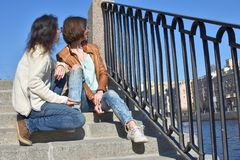 Young ladies tourists sitting together on stair at Fontanka river embankment in Saint Petersburg Russia watching tourist boats on royalty free stock photo