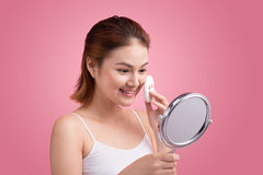 Young lady applying blusher on her face with powder puff and mirror Stock Images