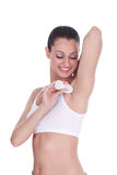 Young lady applying deodorant on armpits Stock Photo