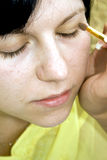 Young lady applying makeup Stock Image