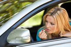 Young lady applying makeup in car Stock Images