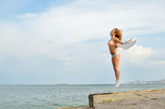 Young lady with arms extended sidewards jumping up royalty free stock photo