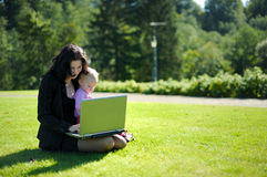 Young lady with a baby and a notebook in a park. Beautiful young lady with a baby and a notebook in a park Stock Photo
