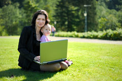 Young lady with a baby and a notebook in a park. Beautiful young lady with a baby and a notebook in a park Stock Image