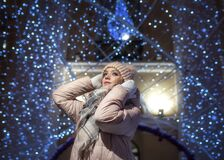 A young lady in beige clothes on a background of blue bokeh from a large Christmas ball