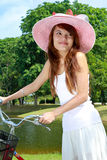 Young Lady with bicycle. Attractive Young Asian woman with bicycle outdoor Royalty Free Stock Images