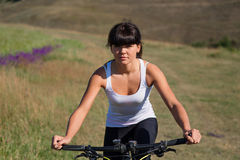 Young lady with bicycle on a spring meadow Stock Image