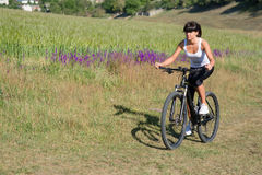 Young lady with bicycle on a spring meadow Stock Photos