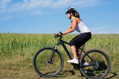 Young lady with bicycle on a spring meadow Royalty Free Stock Images