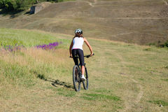 Young lady with bicycle on a spring meadow Royalty Free Stock Photography