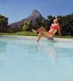 Young lady in bikini sunbathing by poolside. Beautiful young woman sitting by swimming pool and enjoying a sunbath. Caucasian female model in bikini sunbathing Stock Images