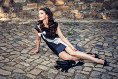 Young lady in black dress sitting on the old street Stock Image