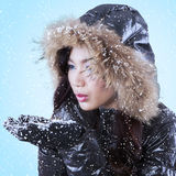 Young lady blowing snow on palms Stock Image