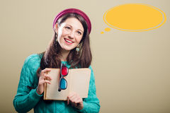 Young lady with book and 3d glasses at speech. Young pretty lady in blue handmade sweater holding book and 3d glasses copyspace with yellow speech bubble Stock Photo