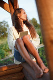 Young lady with book in summerhouse on sunset. Young lady with book sitting in summerhouse on sunset stock photography