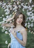 A young lady in the branches of a blooming Apple tree