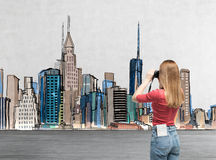 Young lady in casual clothes is taking a pictures of the drawn New York. A concept of modern tourism. Stock Photo