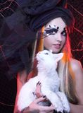 Young lady with cat. Gothic lady with artistic makeup posing witt white cat stock photography