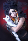 Young lady with cat. Gothic lady with artistic makeup posing witt white cat royalty free stock photography