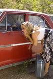 Young Lady Checking Makeup. A young woman checks her makeup in the mirror of a vintage car. Older luggage gives shot an overall vintage feel royalty free stock image