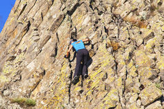 Young lady climbing the rocks Stock Images