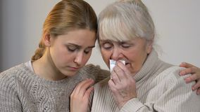 Young lady comforting unhappy crying granny suffering loss, support in family. Stock footage stock video