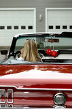 Young lady in convertible sports car. Young blonde lady sitting behind steering wheel of red antique convertible sports car Royalty Free Stock Photos