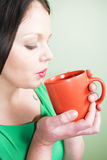 Young lady cools a hot drink. A young brunette lady blows on a mug of coffee or tea Stock Photo