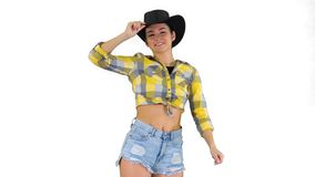 Young lady in a cowboy hat dancing on white background. Medium shot. Young lady in a cowboy hat dancing on white background. Professional shot in 4K resolution stock video footage