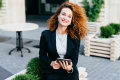 Young lady with curly hair, red painted lips and shining eyes, wearing black suit and shirt, sitting at outdoor cafe with tablet, stock photos