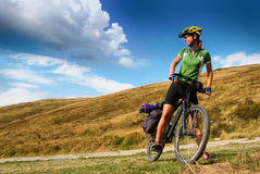 Young lady cycling in the mountains royalty free stock photography