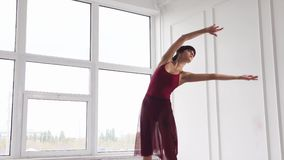 A young lady dances, a woman elegantly raises her arms up during movements stock video