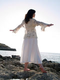 Young Lady Dancing on Sea Shore. Beautiful young lady dancing on rocky sea shore Royalty Free Stock Photo