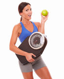 Young lady on diet having positive attitude. On losing weight while holding an apple and weight scale at isolated background royalty free stock photography