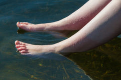 Young lady dipping her feets Stock Images
