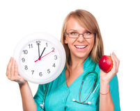 Young lady doctor is holding clock showing one Stock Photo