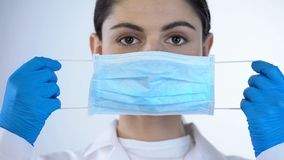 Free Young Lady Doctor Putting On Surgical Mask, Safety While Examining, Closeup Royalty Free Stock Images - 126516929