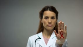 Young lady doctor showing red ribbon sign on hand, AIDS awareness campaign stock photos